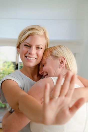 Young happy woman showing engagement ring to her mom