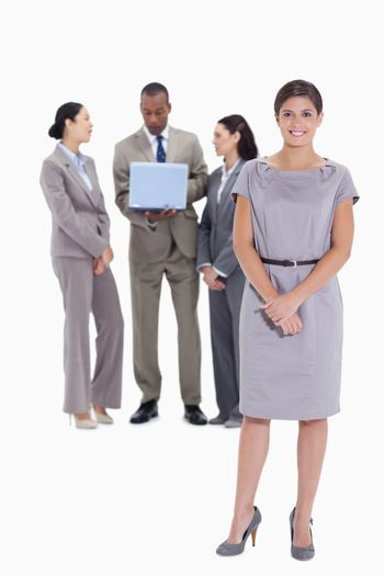 Woman holding her hands with co-workers talking with a laptop in the background