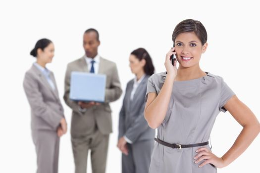 Woman smiling on the phone with one hand on her hip and co-workers talking in the background with a laptop