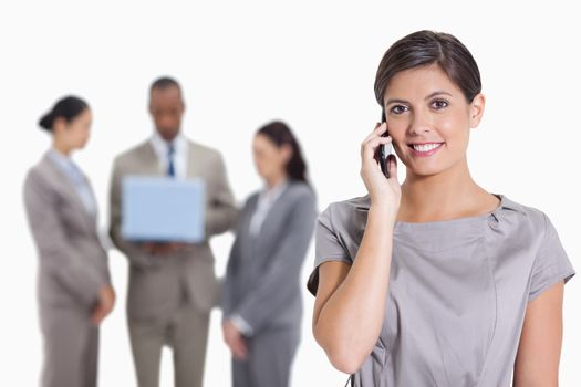 Close-up of a Woman with her head tilted slightly smiling on the phone and three co-workers with a laptop in the background