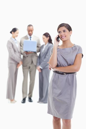 Businesswoman looking up on the phone with co-workers in the background watching a laptop screen