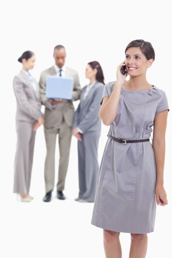 Businesswoman smiling on the phone with one arm along her body and co-workers in the background looking a laptop screen