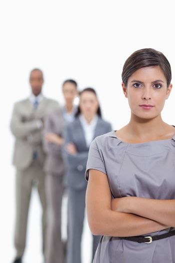 Close-up of a business team crossing their arms and standing behind each other with focus on the foreground woman against white background