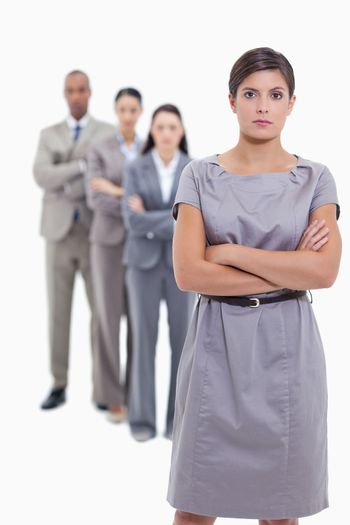 Serious business team crossing their arms and standing behind each other with focus on the foreground woman against white background