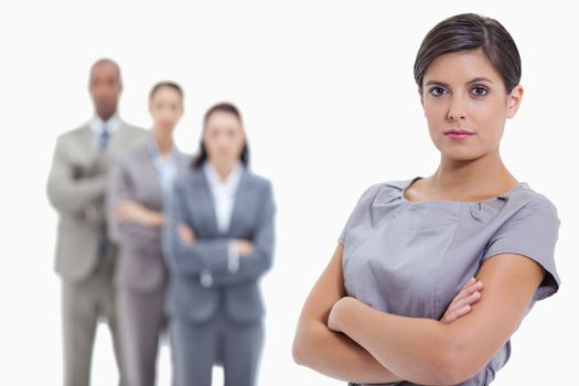 Close-up of a serious businesswoman and a team crossing their arms in background