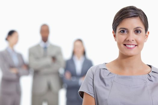 Big close-up of a businesswoman smiling and a team crossing their arms in background