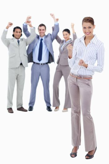 Secretary smiling and clenching her fists with very enthusiastic business people behind her against white background