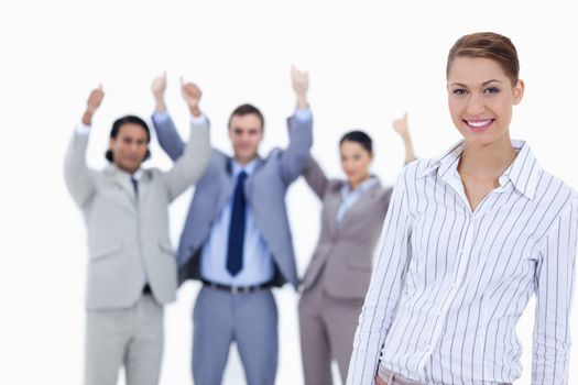 Close-up of a secretary smiling with enthusiastic business people with their thumbs up in background