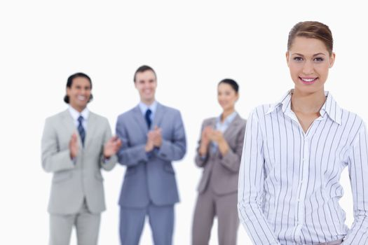 Close-up of a woman smiling with business people applauding in background