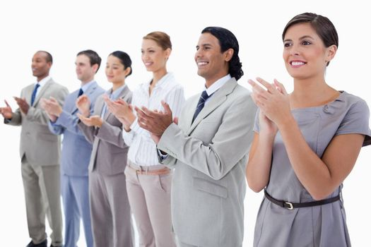 Close-up of colleagues smiling and applauding with focus on the first two people against white background