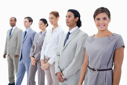 Close-up of a businesswoman smiling while looking straight and colleagues looking towards the left side against white background