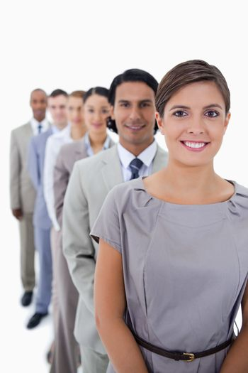 Close-up of colleagues in a single line smiling and looking straight with focus on the first woman against white background