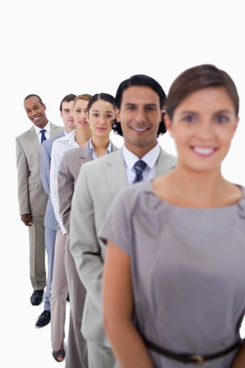 Close-up of workmates in a single line looking straight with focus on the last man against white background