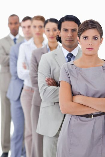 Close-up of serious workmates crossing their arms in a single line with focus on the first woman