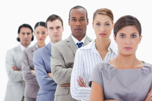 Big close-up of a serious business team in a single line crossing their arms with focus on the second woman