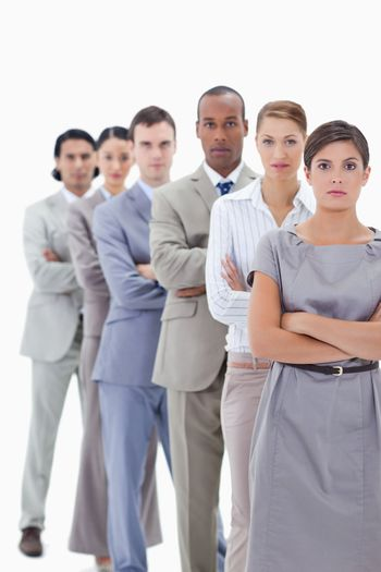 Close-up of a serious business team in a single line crossing their arms with focus on the first woman