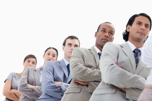 Low-angle shot of a business team crossing their arms in a single line against white background