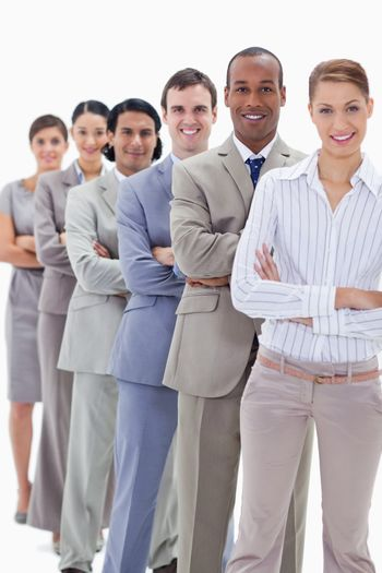 Smiling workmates dressed in suits crossing their arms in a single line with focus on the first man