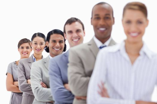 Close-up of smiling workmates dressed in suits crossing their arms in a single line with focus on the last two people