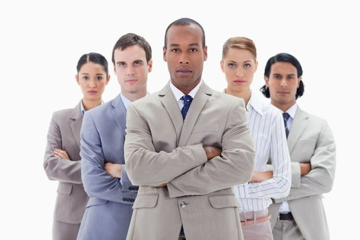 Close-up of a serious business team crossing their arms against white background