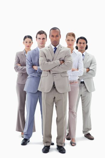 Determined business team crossing their arms against white background