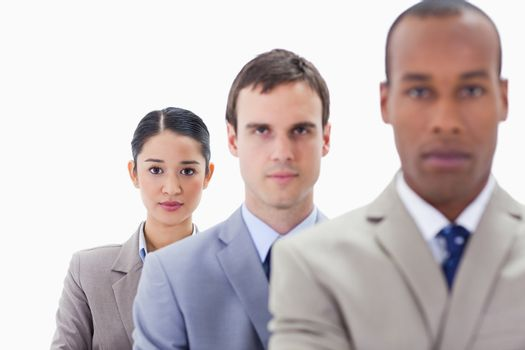 Big close-up of serious colleagues in a single line looking straight with focus on the woman