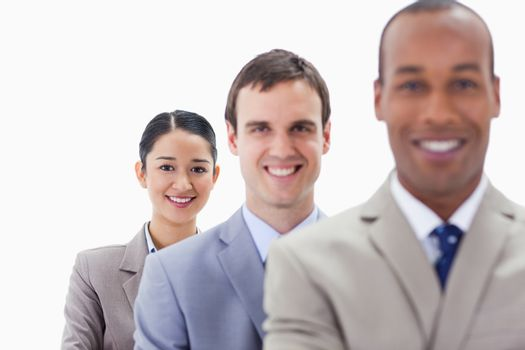 Big close-up of workmates smiling in a single line with focus on the woman