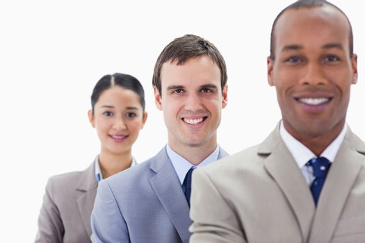 Big close-up of colleagues smiling in a single line with focus on the middle man