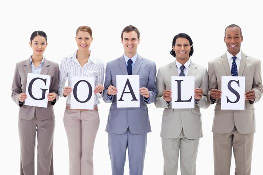Happy business team holding the letters of GOALS against white background