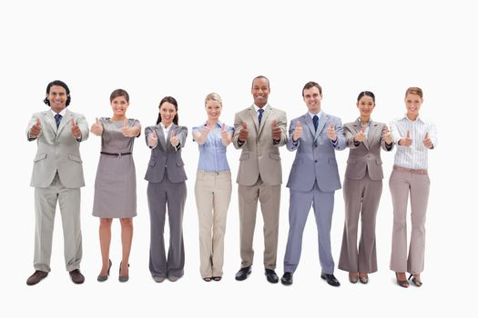 Smiling business team side by side with their thumbs up against white background