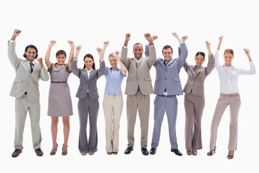 Happy business team raising their arms against white background