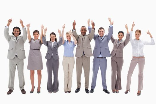 Business team raising their arms with the thumbs up against white background