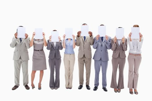 Business people hiding their faces with white support for letters against white background