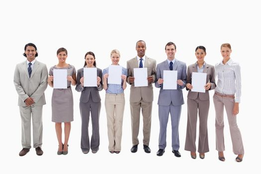 Happy business people holding six white supports for letters against white background