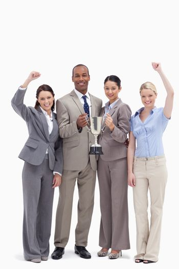 Happy business team holding a cup and raising arms against white background