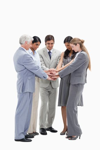 Business people putting their hands on each others against white background