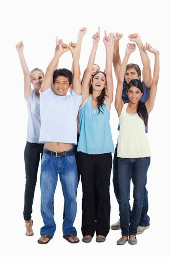 People smiling together and raising their arms against white background