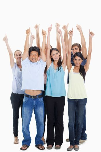 People smiling together raising their arms with their thumbs-up against white background