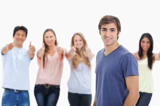 Man smiling with people approving behind him against white background