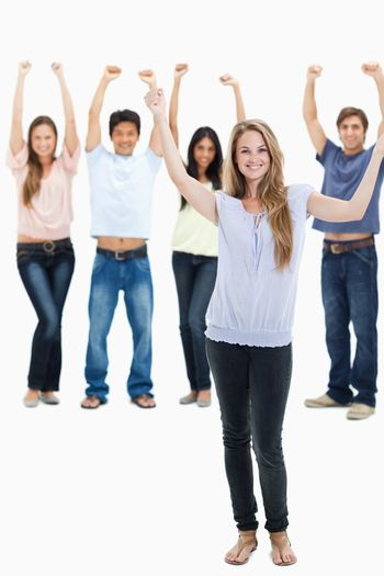 People in jeans with their arms raised against white background