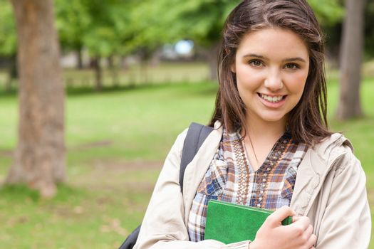 Portrait of a first-year student holding a textbook while posing in a park