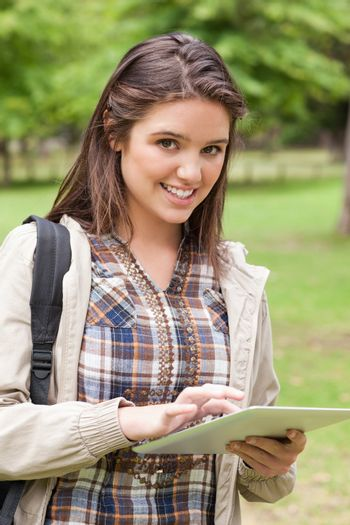Portrait of a first-year student using a touch pad in a park