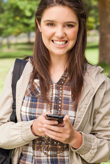 Portrait of a cute teenager with a smartphone in a park