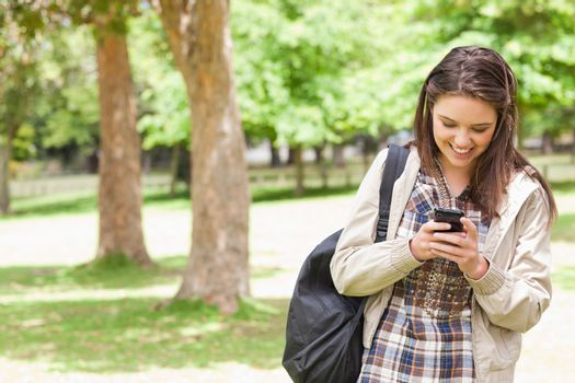 Young student using a smartphone in a park