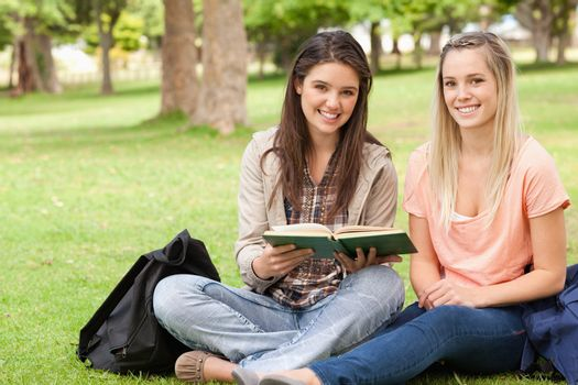 Female teenagers sitting with a textbook in a park while looking at camera