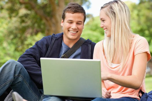 Laughing young people sitting while using a laptop in a park