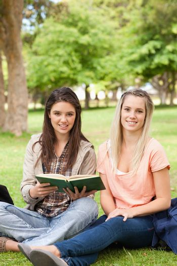 Portrait of female teenagers sitting with a textbook
