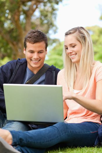 Close-up of young people sitting while using a laptop in a park
