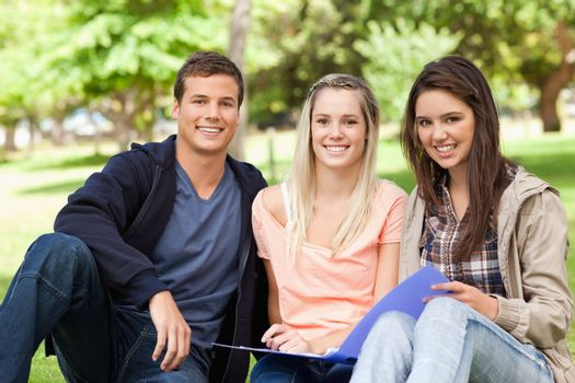 Portrait of three teenagers studying together in a park