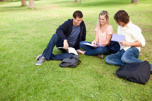 High angle-shot of three students in a park studying